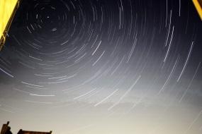 Foto zeigt Sternespuren am Himmel - bei langer Belichtung wird wegen der Erddrehung ein Kreis daraus. Astronomie.