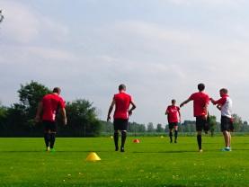 Foto zeigt Sport-Coach beim Training einer Fußballmannschaft. Symbolisch für Bewerbungs-Coaching.
