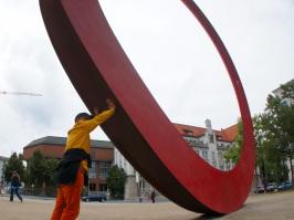 Bewerber schiebt riesige Rad-Skulptur vor sich her. Bewerbung als Herausforderung.